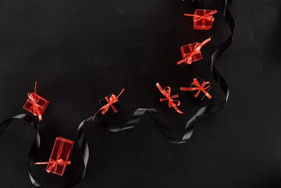 Top View of Black And Red Decorative Gift Boxes With Bows Near Ribbon on Black Background