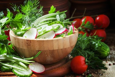 Vegetarian salad with radishes, cucumber, tomato, wild garlic, green onions and herbs
