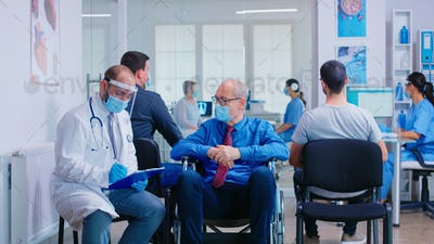 Medical staff with face mask talking with disabled senior man in waiting area