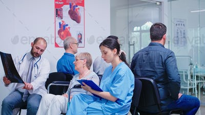 Medical staff discussing diagnosis with disabled senior woman