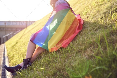 Unrecognizable woman with a rainbow flag sitting on the grass