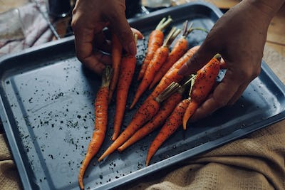 Chef mixing the carrots with seasoning on the baking tray