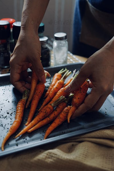 The carrots mixed with seasoning on the baking tray
