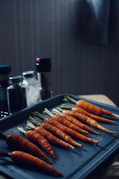 The carrot mixed with seasoning on the baking tray