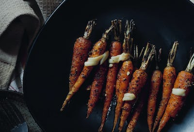 The baked carrots with cheese serving on black plate