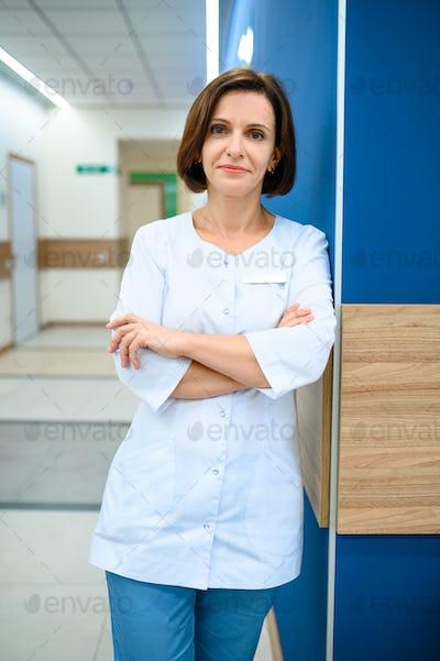 Female doctor standing in clinic corridor