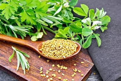 Fenugreek in spoon with herbs on black board