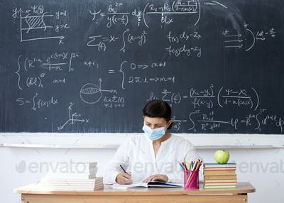 Teacher in the classroom wearing mask. Learning during coronavirus pandemic concept.