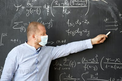 Male teacher in the classroom wearing mask. Learning during coronavirus pandemic concept.