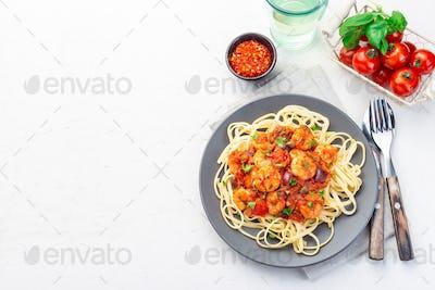 Shrimp linguine Puttanesca pasta with shrimps in tomato sauce, horizontal, copy space