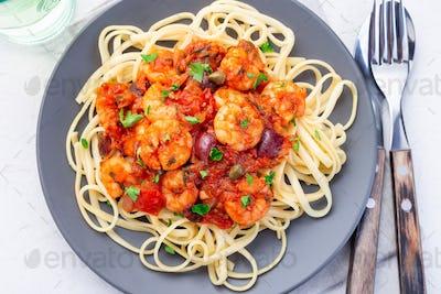 Shrimp linguine Puttanesca pasta with shrimps, top view, horizontal