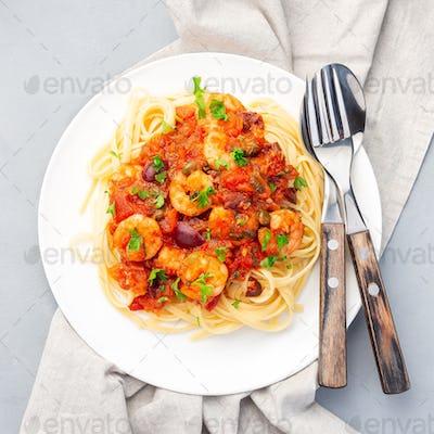 Shrimp linguine Puttanesca pasta with shrimps, on white plate, top view, square
