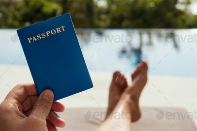 Man Holds A Passport In His Hand On The Tropical Background