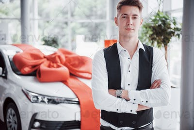 A handsome man is a buyer standing next to a new car at the dealer center and looking at the camera.