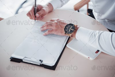 Young man signs documents in the office, successful sales