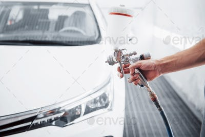 gun with paint in the hands of a man to paint a car