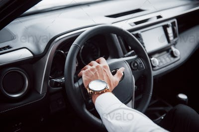 A young man sits in a newly bought car holding his hands on a rudder