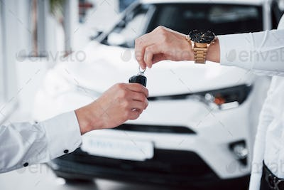 sales manager in suit selling the car to the customer.