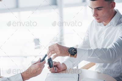 A young man signs documents in the office, successful sales and key transfers to the client