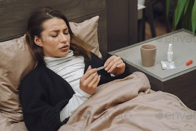 Sick woman with headache sitting at home