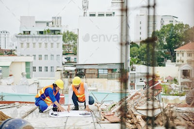Builders discussing plan of works