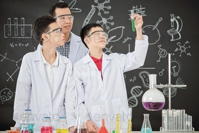 Proud schoolboy showing test-tube