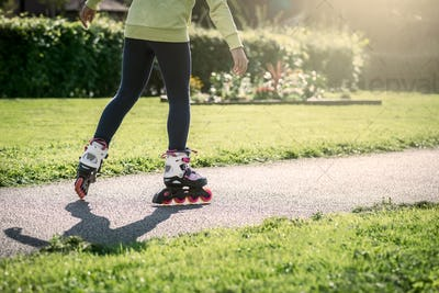 Teenage girl is skating on roller blades in the park