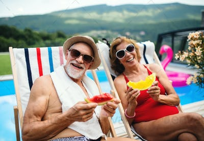 Cheerful senior couple sitting by swimming pool outdoors in backyard