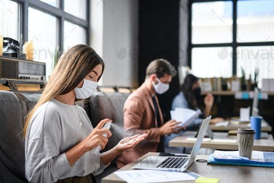 Portrait of young businesspeople with face masks working indoors in office, disinfecting hands