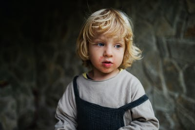 Close-up portrait of small boy standing outdoors, stone wall in the background
