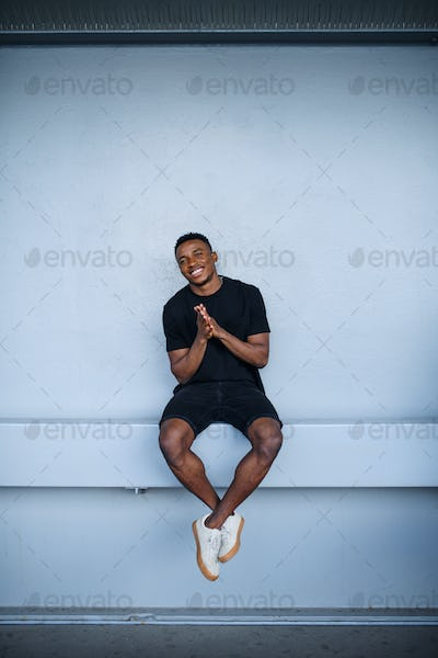 Cheerful young black man sitting against wall background