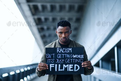 Man with written sign standing outdoors, black lives matter concept