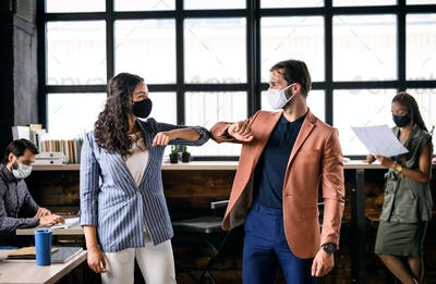 Young businesspeople with face masks working indoors in office, greeting