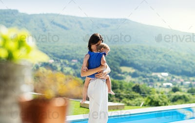 Young mother holding small daughter outdoors in backyard garden