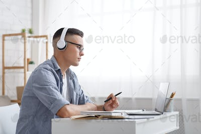 Online education and work at home. Young man in headphones holds pen and looks at laptop, sitting at
