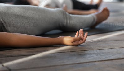 Unrecognizable black female practicing yoga in studio, lying in corpse pose, cropped