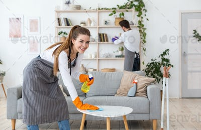 Smiling woman in gloves wipe table with spray, man wipes dust with brush in living room