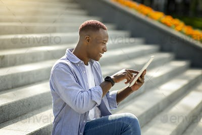 Millennial black man browsing internet on tablet computer while sitting on stairs outside