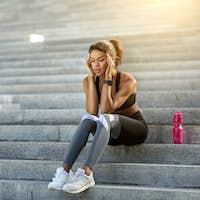 Black woman having headache during training at park