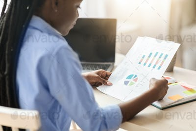 Concentrated black businesswoman checking financial reports, economic graphs and charts at workplace