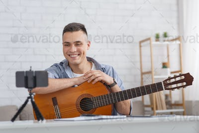 Online music lesson. Smiling guy with guitar looks at smartphone camera