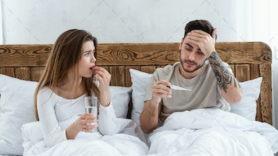 Woman drinking pill, holding glass of water and looking at husband, man touches forehead and looks