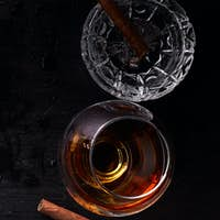 Banner of Glass of whiskey with smoking cigar on dark wooden table.