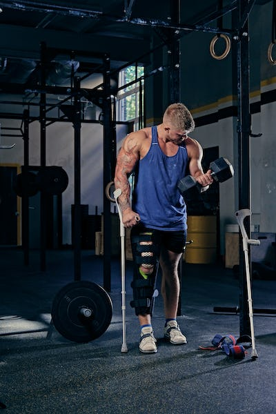 Bodybuilder on crutches holds dumbbell.