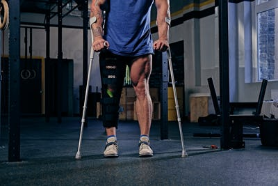 Bodybuilder's leg in bandage with crutches.
