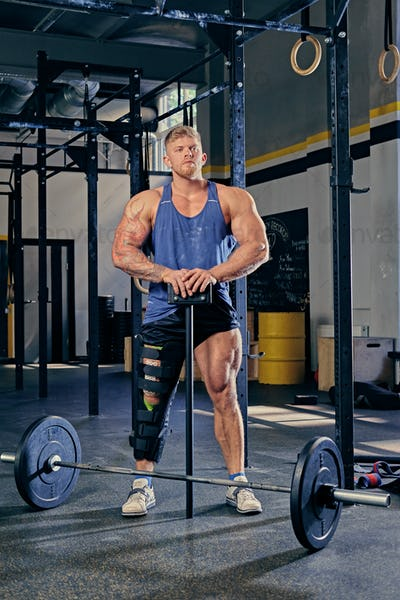 Bodybuilder with injured leg holds barbell.