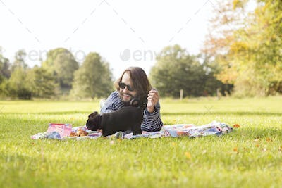 Happy young man with puppy relaxing on picnic blanket at field
