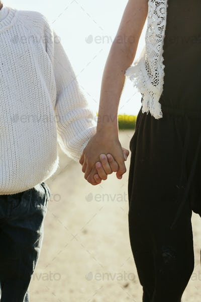 Midsection of siblings holding hands outdoors