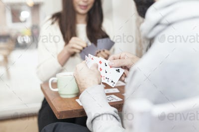 Midsection of couple playing cards in coffee shop