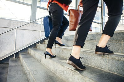 Businesswomen with luggage moving up steps of railroad station